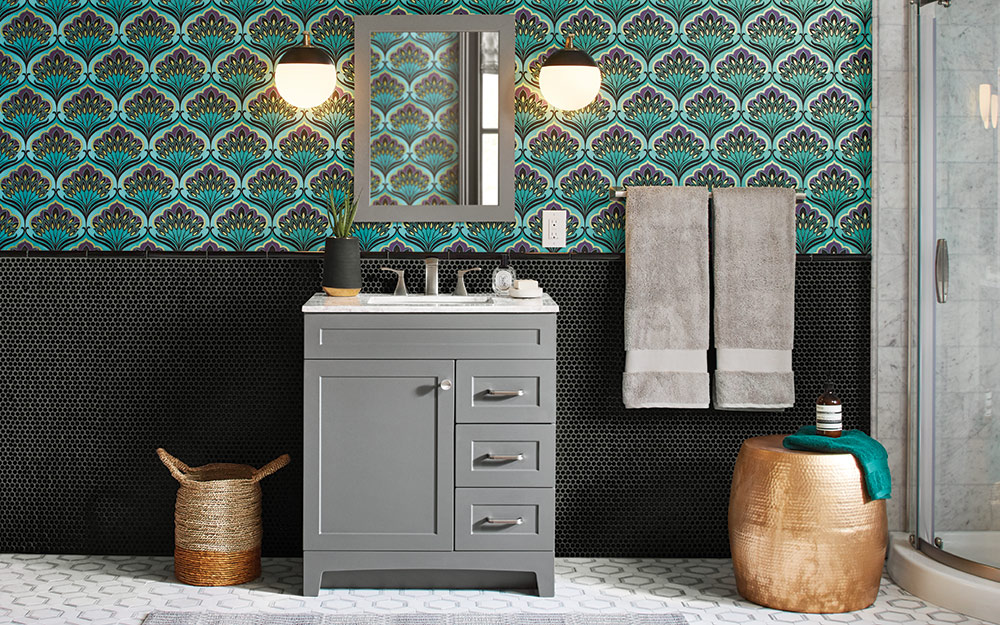 A bathroom with wallpaper and tile on the wall features a vanity and coordinating towels.