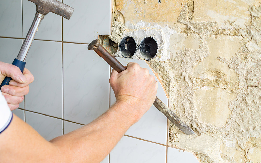 A hammer and chisel are used to remove tile from a wall to remodel a bathroom.
