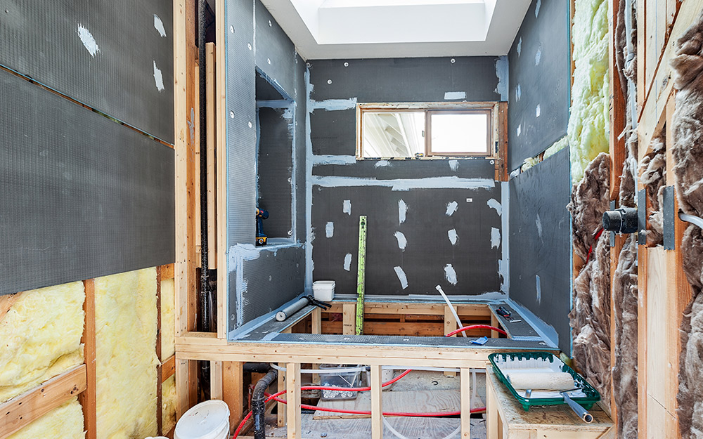 Exposed walls while remodeling a bathroom shows insulation and blocking between wall studs.
