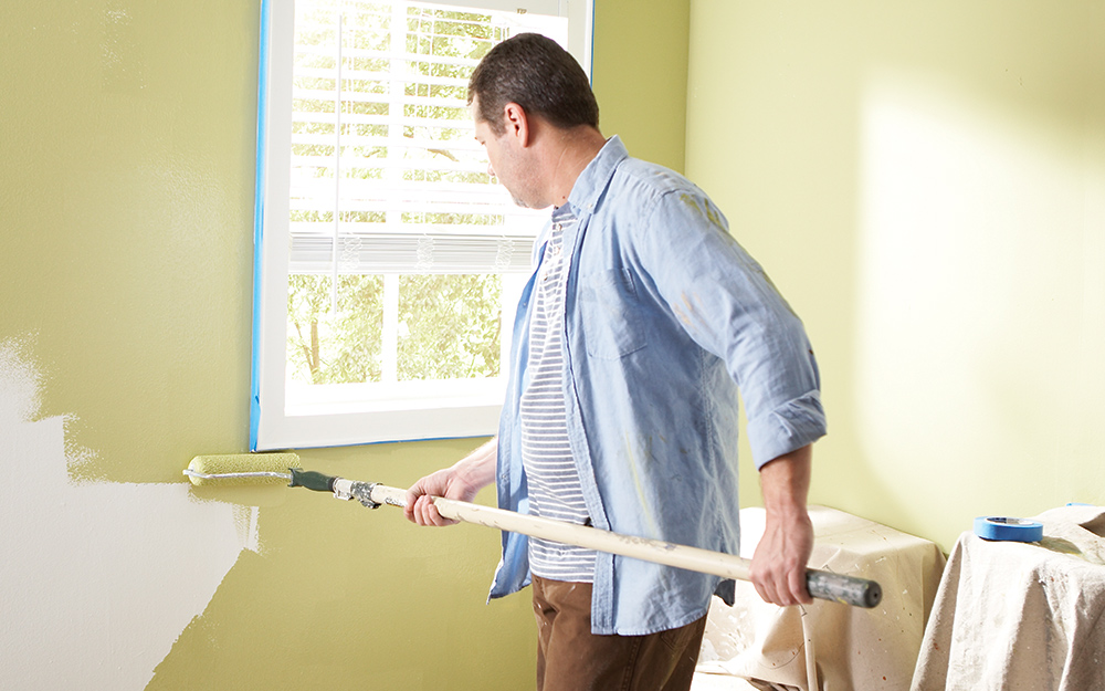 A roller is used to apply paint on a wall while remodeling a bathroom.