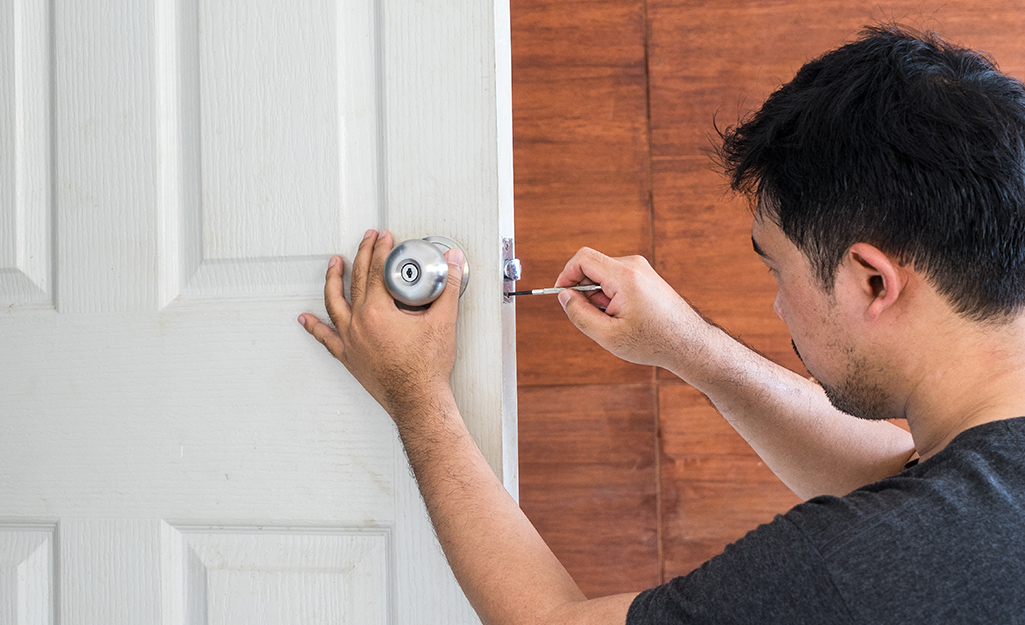 A person getting ready to remove a door knob.