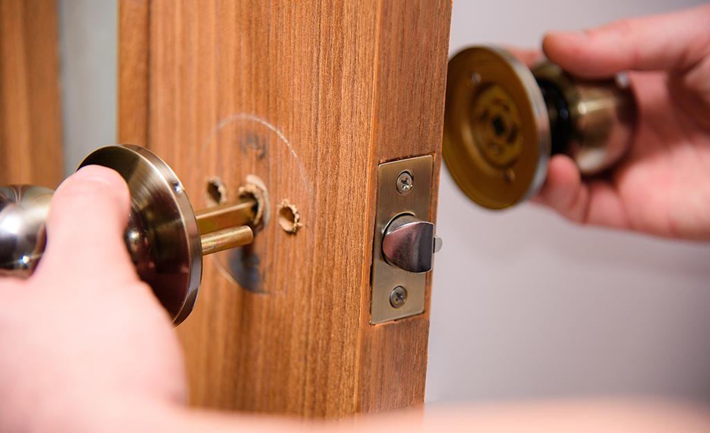 A door knob being removed from a door.