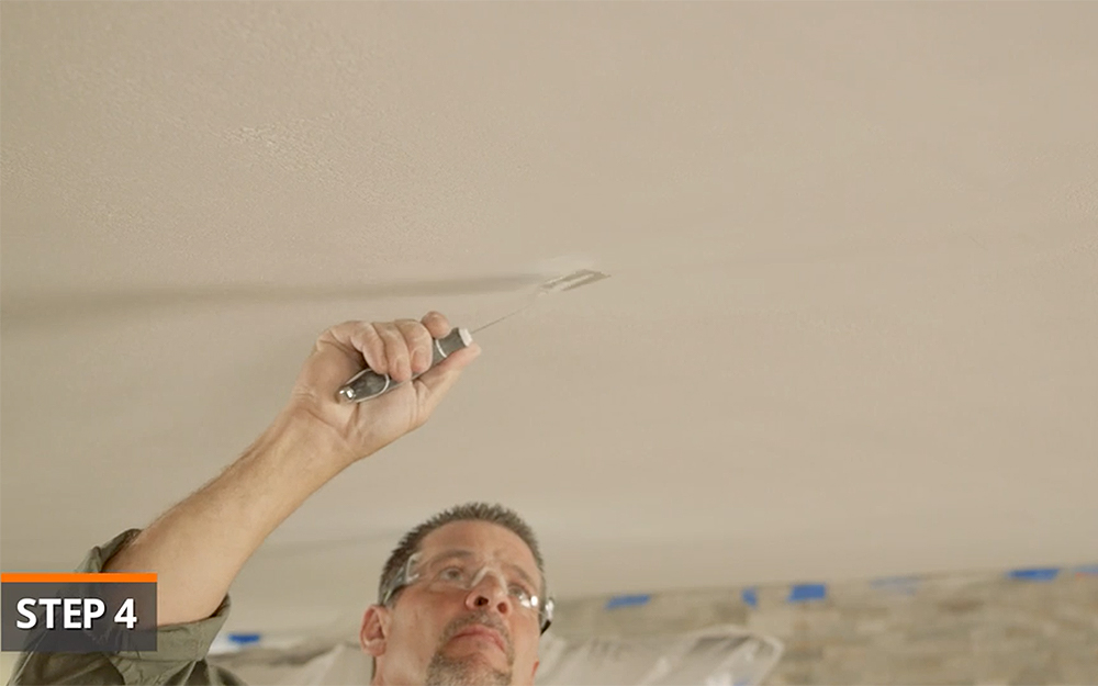 A man patches a hole in the ceiling.