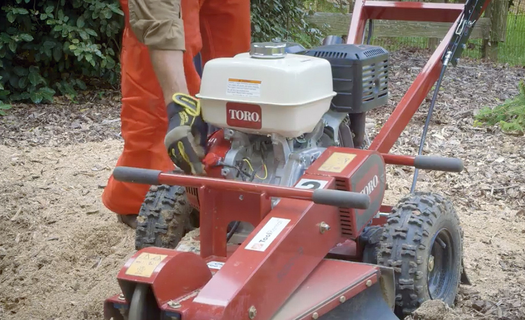 A man wearing work gloves turns a switch on the front of a red tree stump grinder after stump removal is complete.