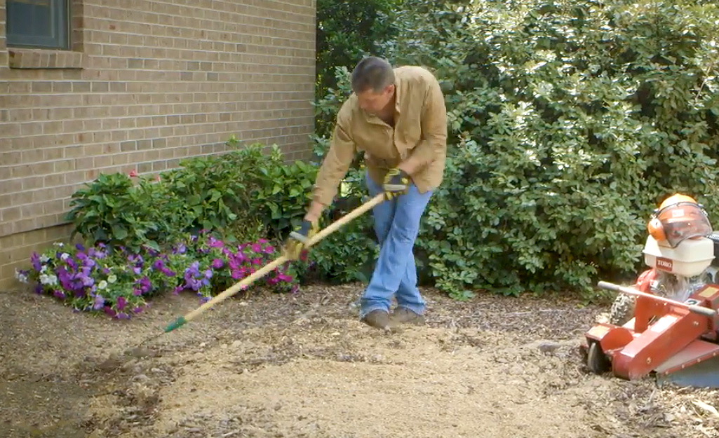 A man wearing jeans, a light brown shirt and work gloves rakes mulch over the area where the tree stump once stood.