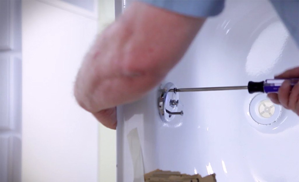 A person attaching the drain on a new tub.