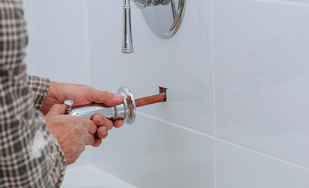 A person disconnecting the drain flange above a bathtub.
