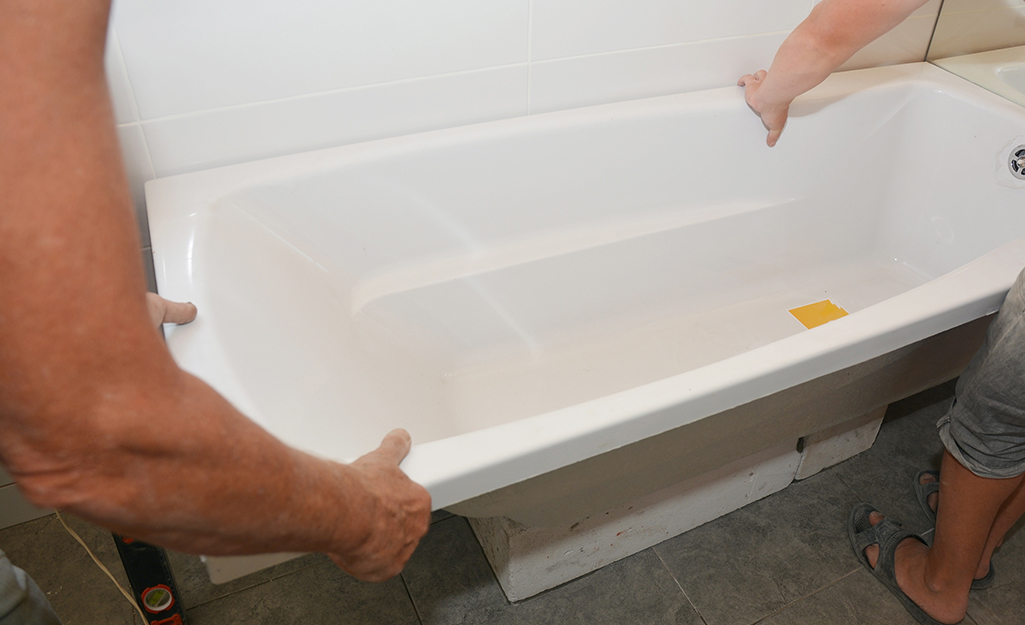 Two people removing a tub from a wall.