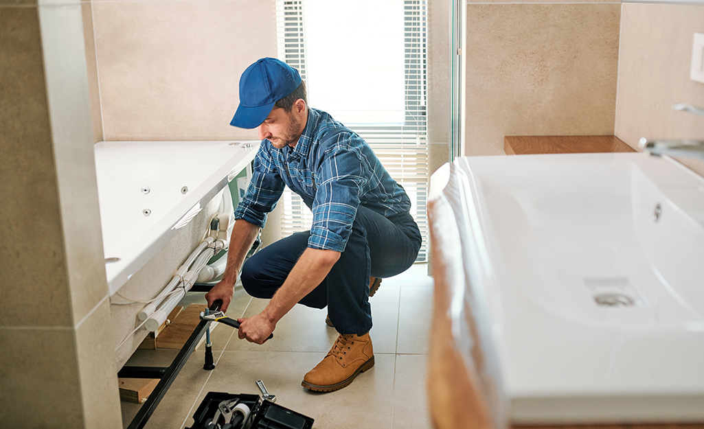 A man preparing a new tub for placement in a bathroom.