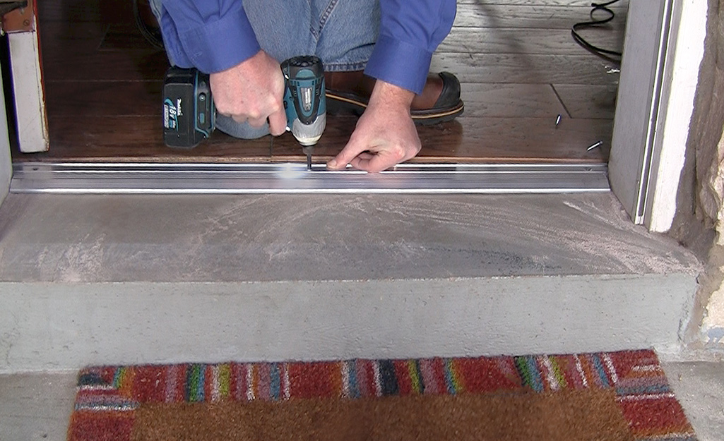 A person uses a power drill to install a metal threshold.