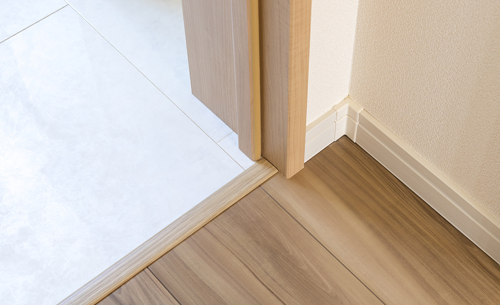 An interior threshold between a tiled room and a room with wood floors.