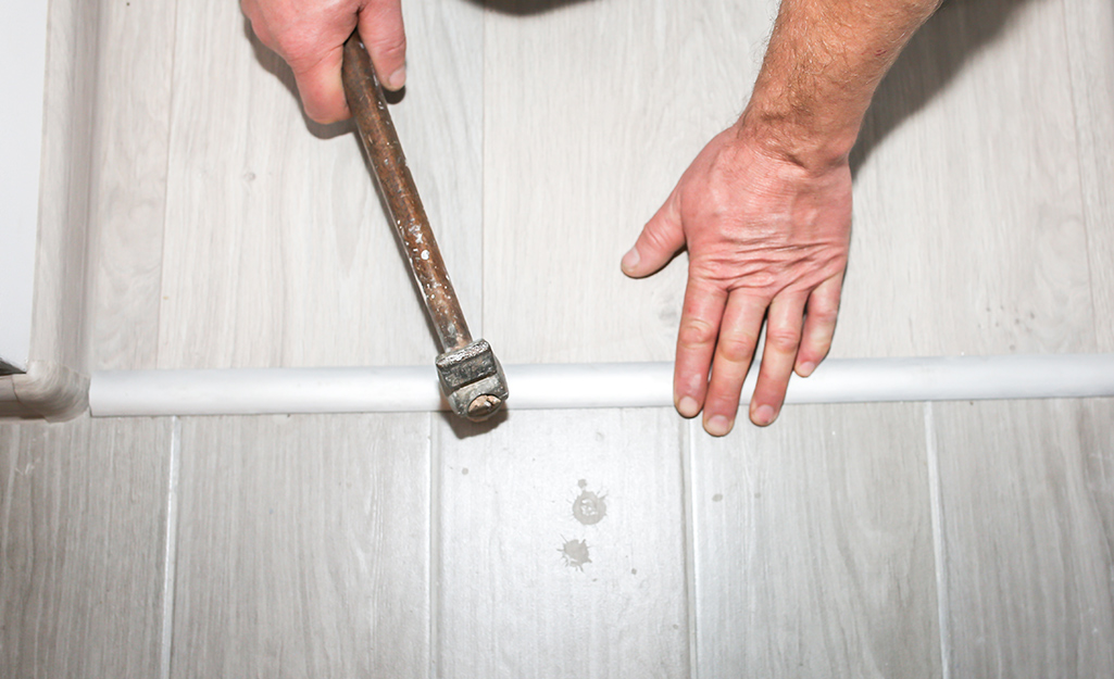 A person uses a hammer to tap an interior threshold into place.