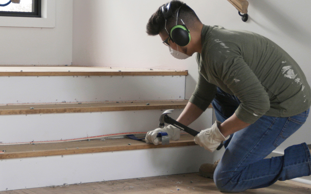 a man removing tack strips from a stair