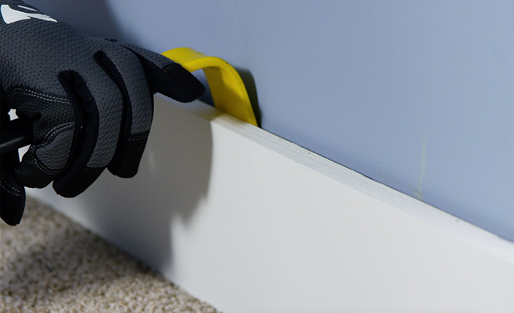 A person removing a baseboard with a pry bar.