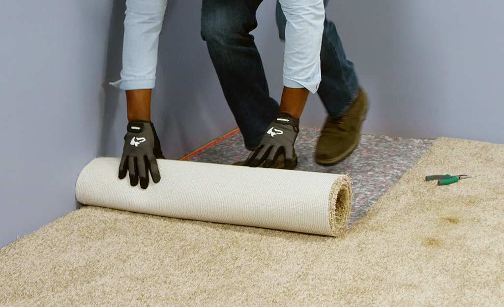 A person removing and rolling up a strip of carpet.