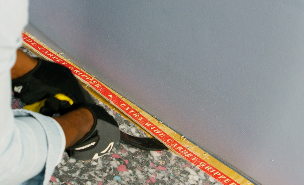 A person using a pry bar to remove carpet tack strips.