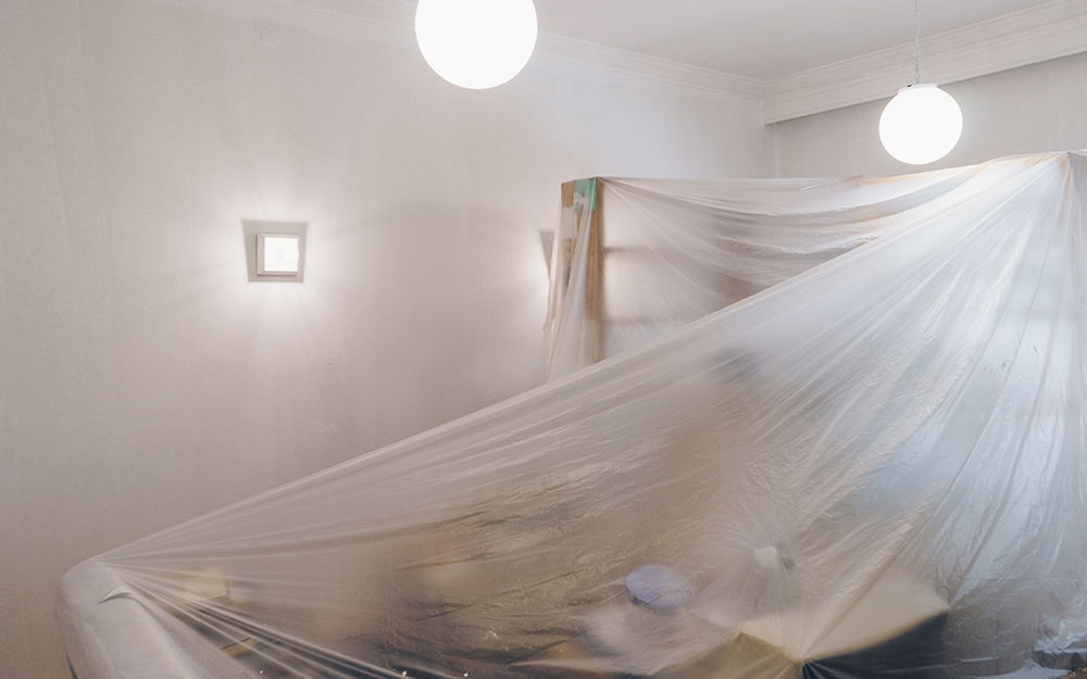Protective sheeting covers the furniture in a room.