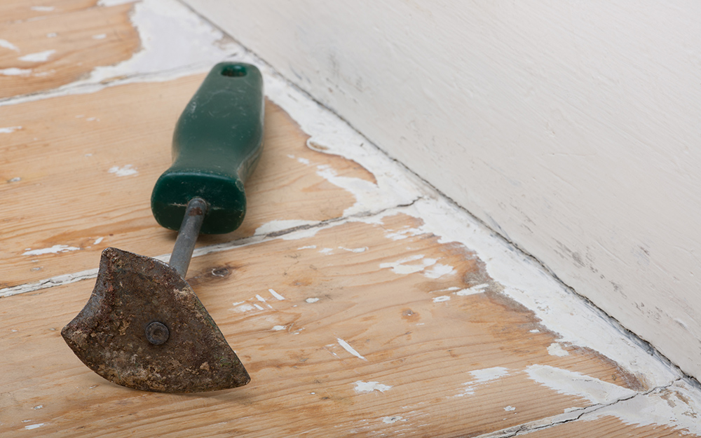 A scraper tool lies on a floor near a wall where molding was removed.