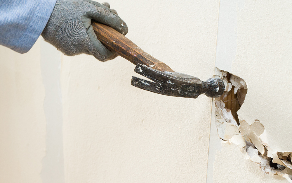 A person uses a claw hammer to make holes in drywall.