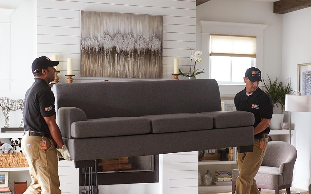 hai người đàn ông di chuyển một chiếc ghế dài