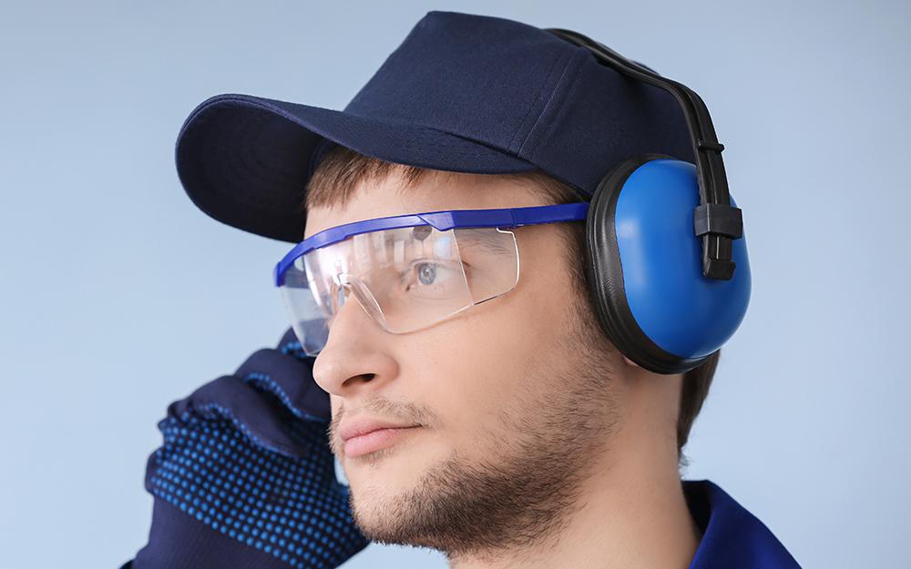 người đàn ông đội mũ và đeo găng tay và đeo kính bảo hộ và bảo vệ tai