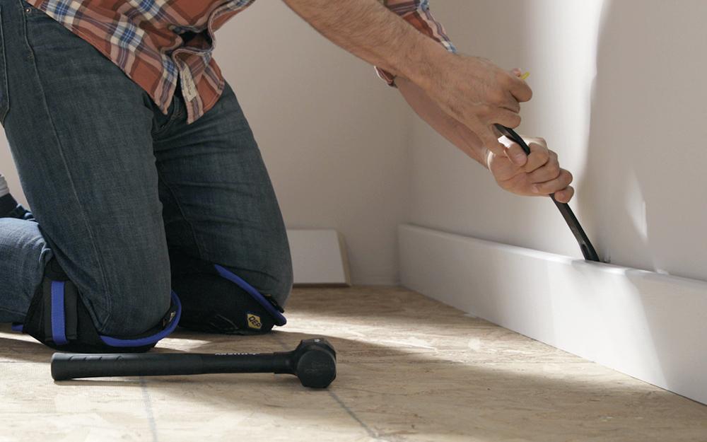 người sử dụng một thanh cạy để loại bỏ trang trí và ván chân tường