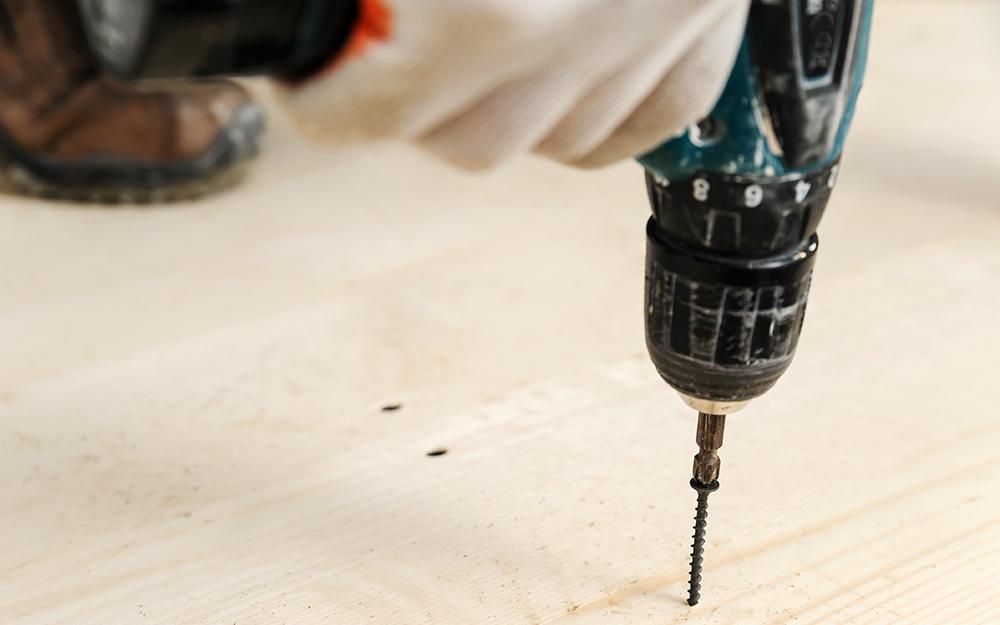 người sử dụng máy khoan trên sàn gỗ
