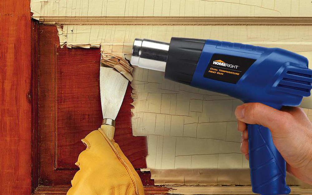 Person using a putty knife to gently remove the softened paint.