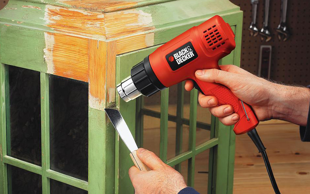 Person uses a specialty scraper to remove the paint from a problem area.