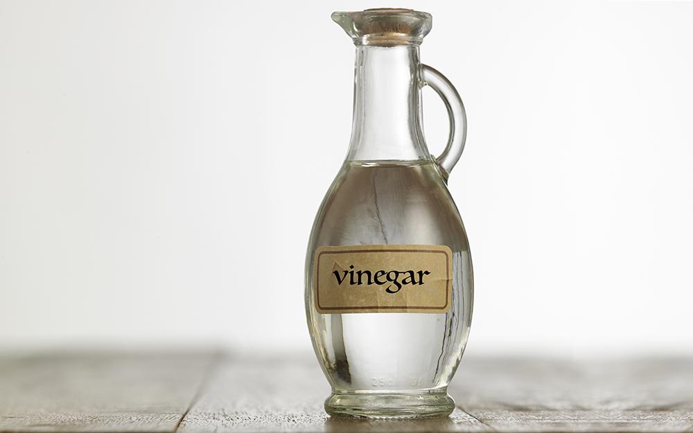A cruet of vinegar sits on a table.