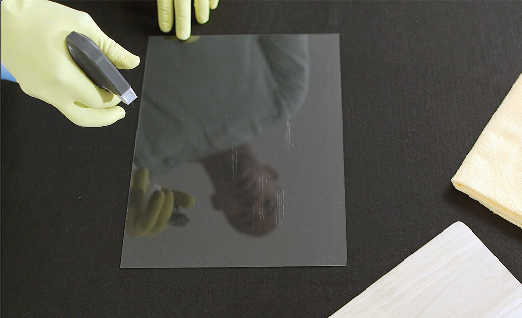 Person wearing yellow rubber gloves sprays glass cleaner on a window.