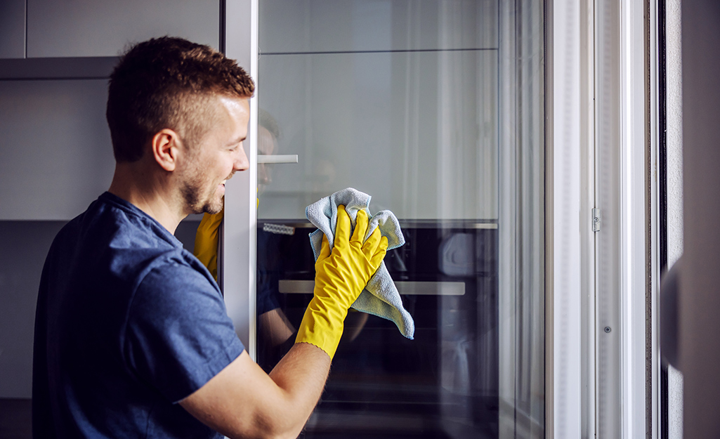 Man wearing yellow rubber glove smiles as he cleans a glass window with cloth.