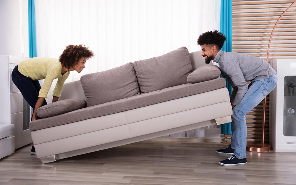 A couple moving a sofa.