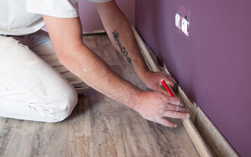 A person removing baseboards.