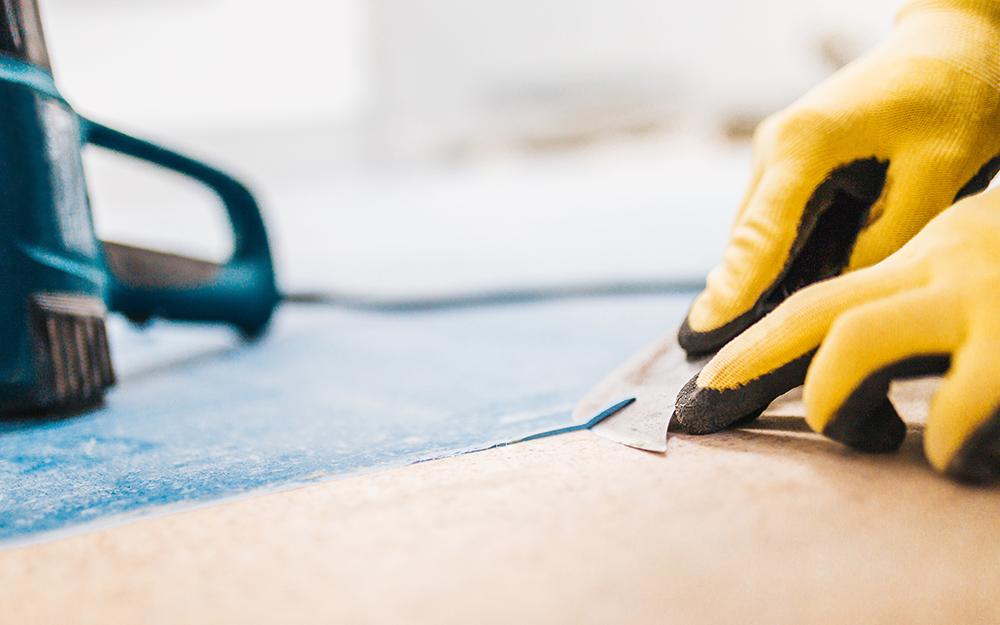 A person cutting vinyl flooring.