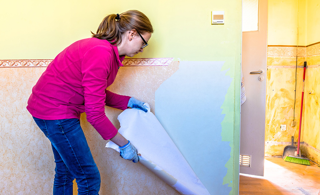 A woman removing wallpaper.