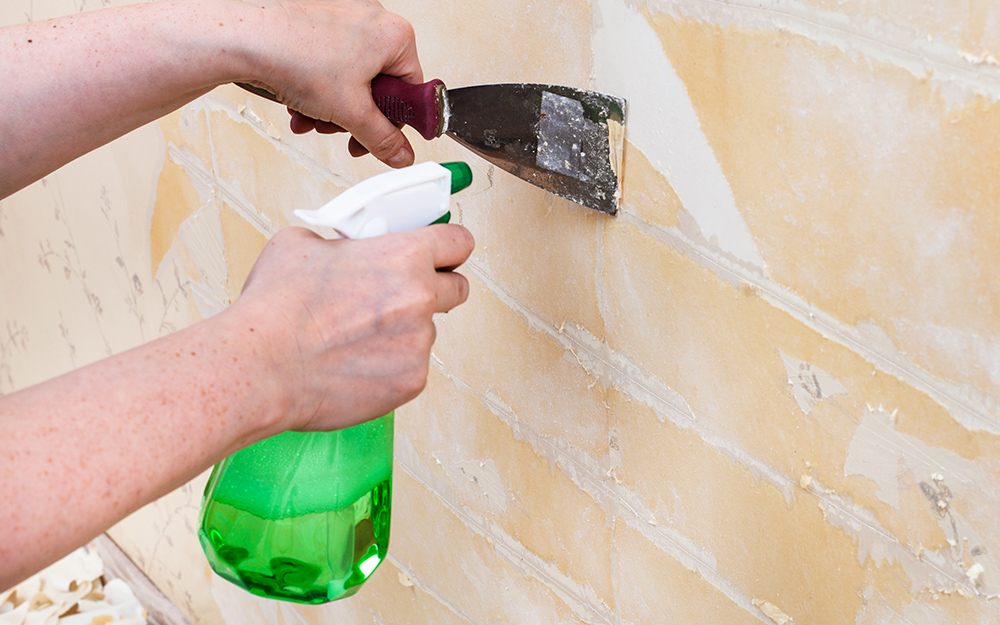 A person using a spatula and liquid wallpaper remover to remove wallpaper