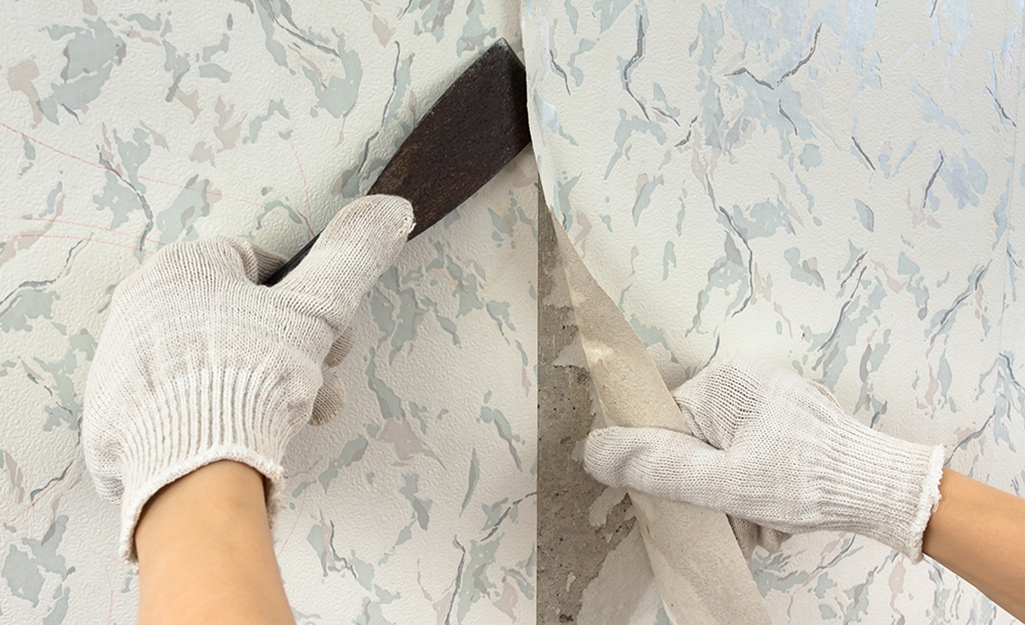 A person wears gloves while removing wallpaper with a scraper.