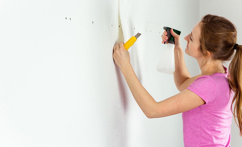 A person applies wallpaper remover with a spray bottle.