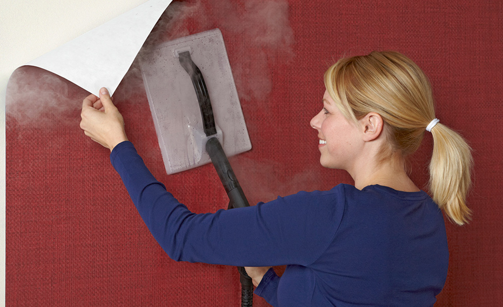 A person uses a steamer to remove wallpaper.
