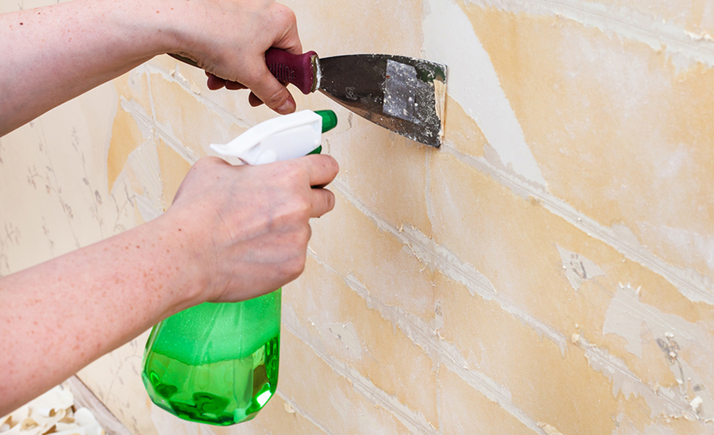 A person uses a scraper to remove the remnants of wallpaper from a wall.