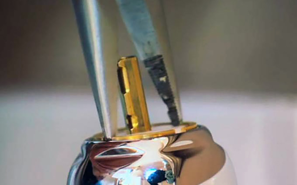 Needle nose pliers loosen the adjustment ring for a ball faucet.