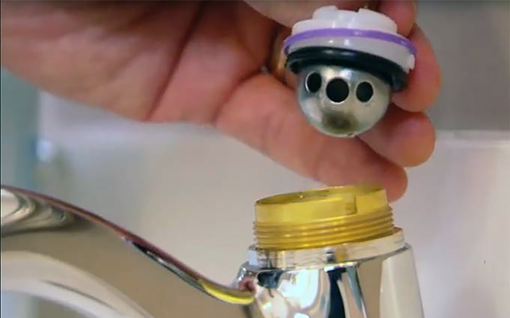 The ball, packing washer and cam assembly is removed from a ball faucet.