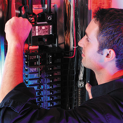 A person working on the circuit breakers inside of an electrical panel.