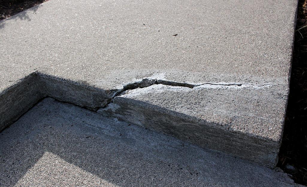 A deep crack runs through a concrete step.