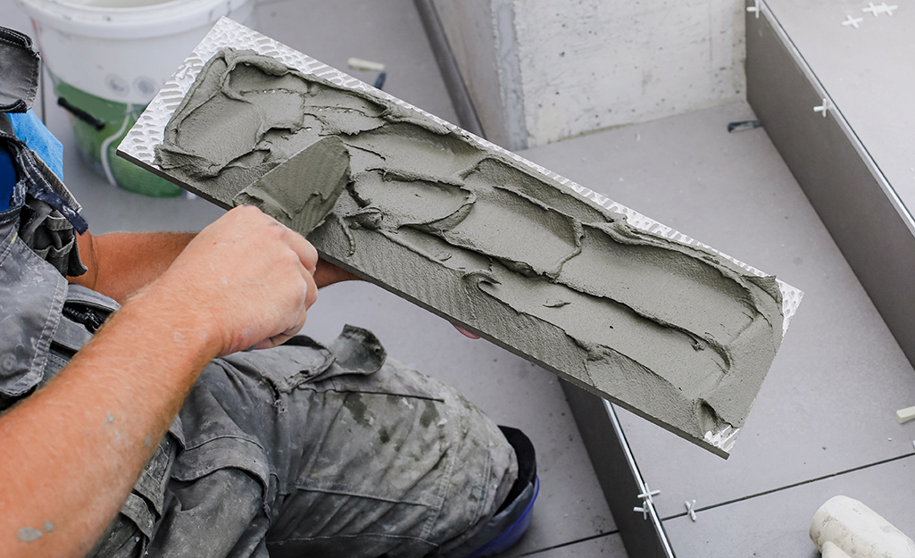 A person uses a trowel to apply concrete repair material to steps.
