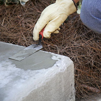 A person smooths a repair patch on a concrete step.