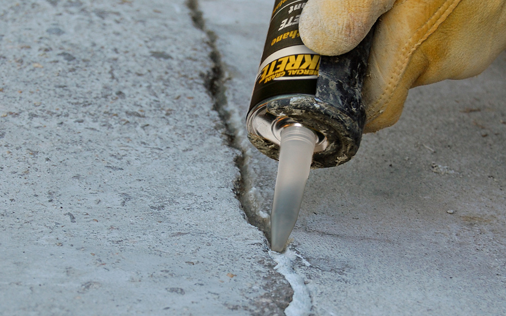 Someone squeezing a tube of filler into cracks in a concrete driveway.