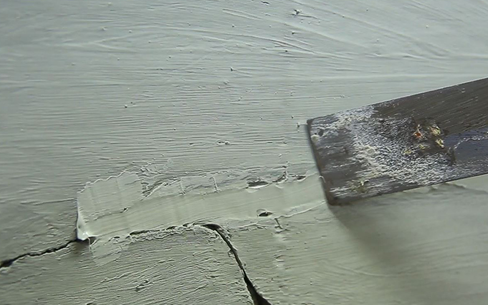 Someone using a putty knife to smooth filler over cracks in a concrete driveway.