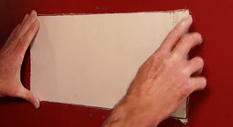 Person inserts drywall patch to perfectly fit into cut-out.